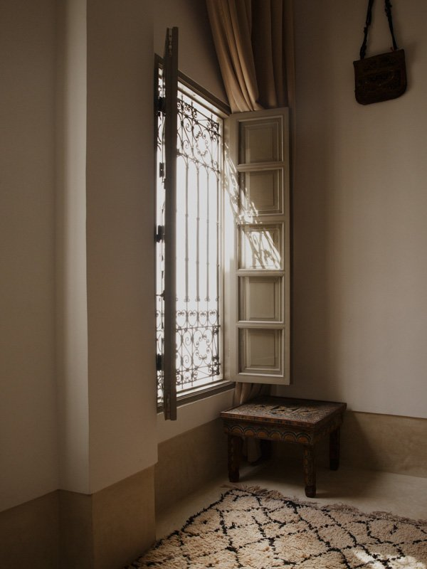 Open wooden window shutters at Moroccan hotel, decorative wrought iron grill