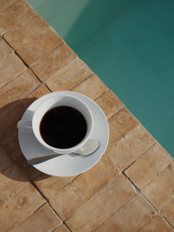 Cup of Tea with Saucer and Teaspoon on edge of Swimming Pool