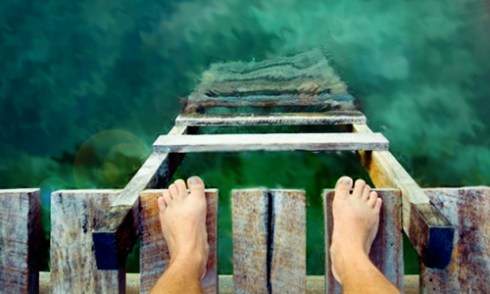 feet on the edge over water