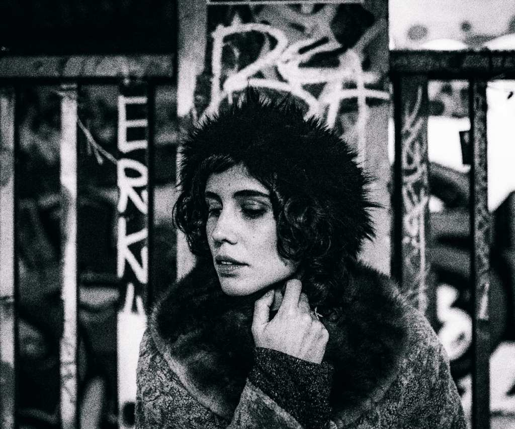 A black and white close up photograph of a woman looking down, with graffiti behind her