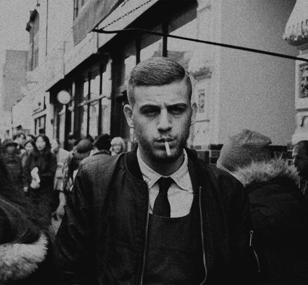 A black and white photograph of a man smoking as he walks down the street
