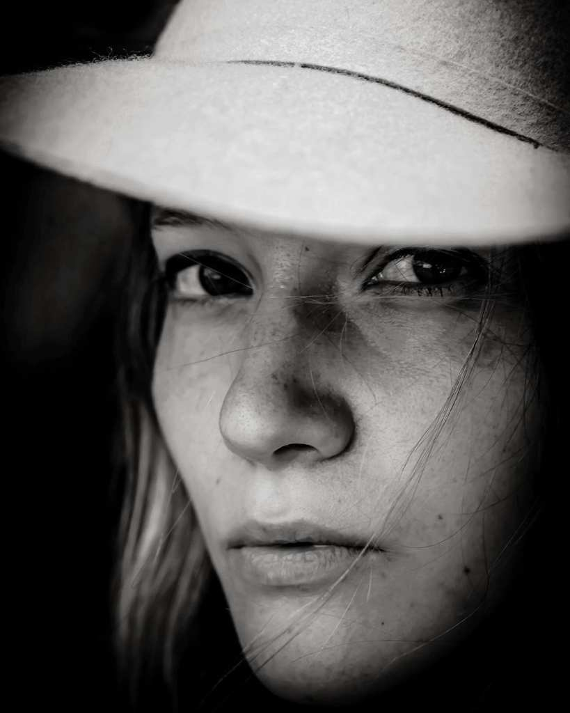 A close up black and white photograph of a young woman wearing a hat