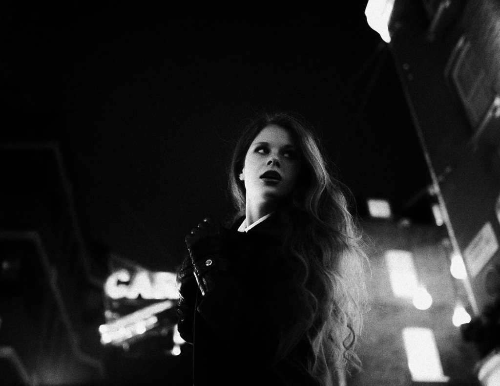 A black and white image of a woman looking away from the camera on a busy street