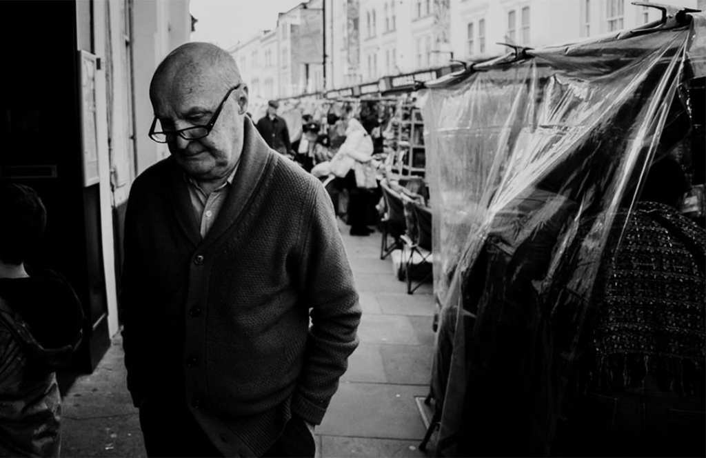 A black and white photograph of a man wearing glasses walking through a market