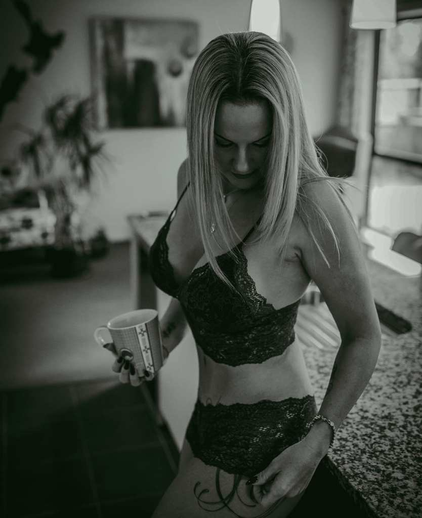 A black and white photograph of a woman wearing lingerie in her kitchen