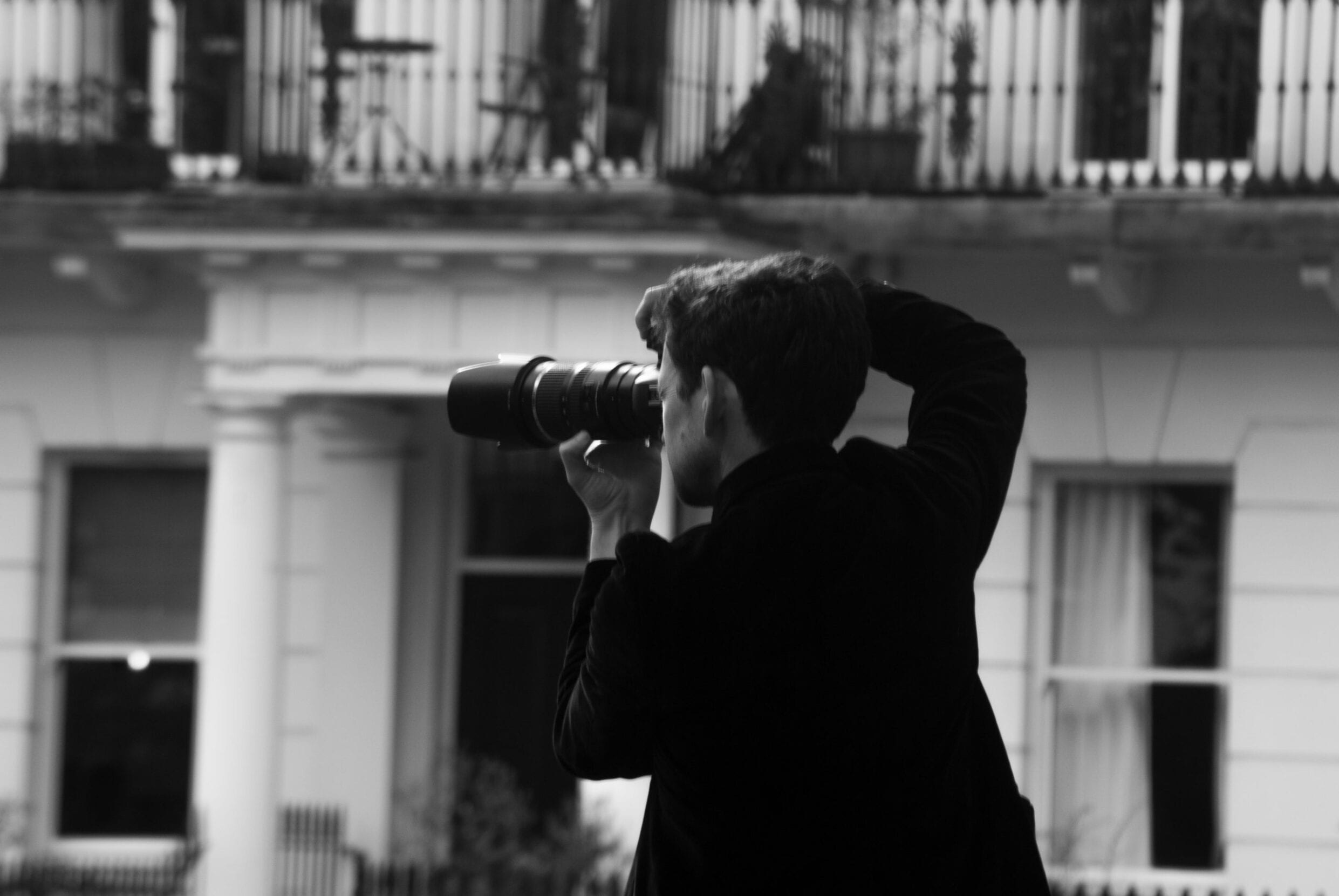 A man holds a camera with big white houses in the background
