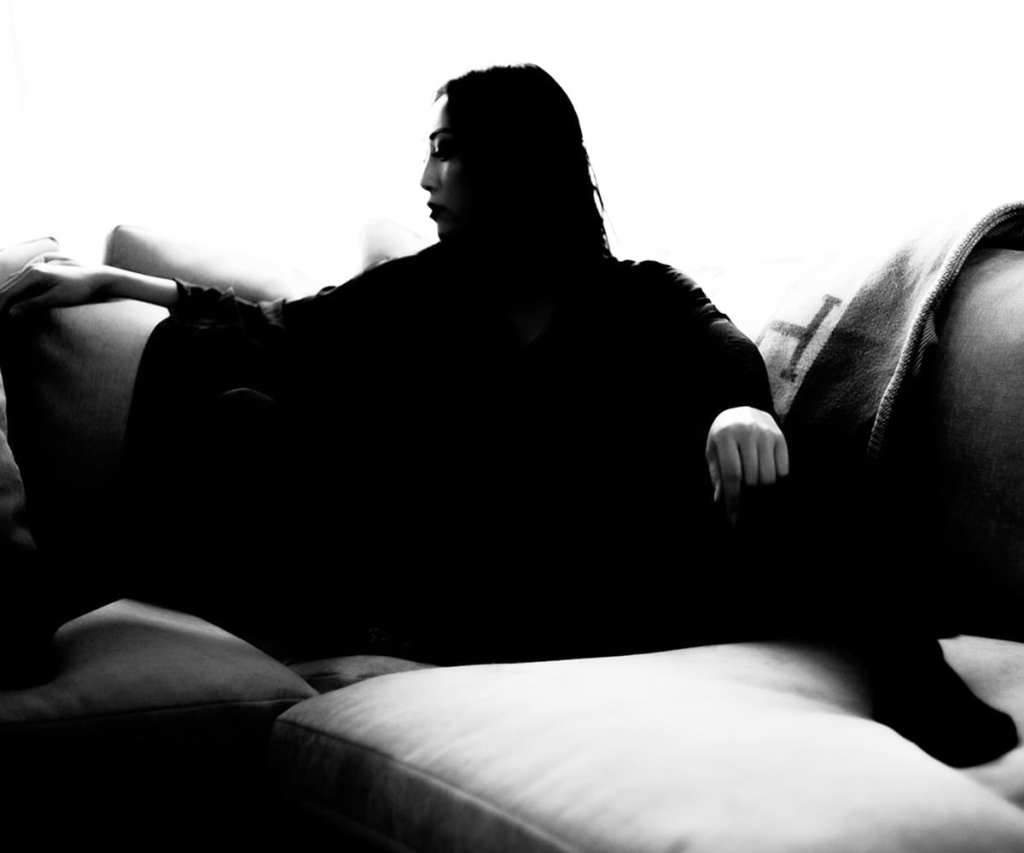 a black and white photo of a woman on a sofa