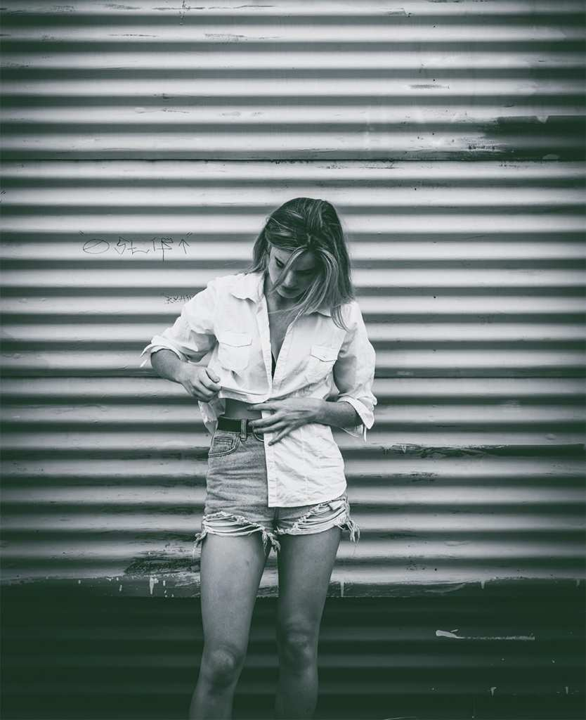 A black and white photo of a woman tucking her white shirt into her jean shorts