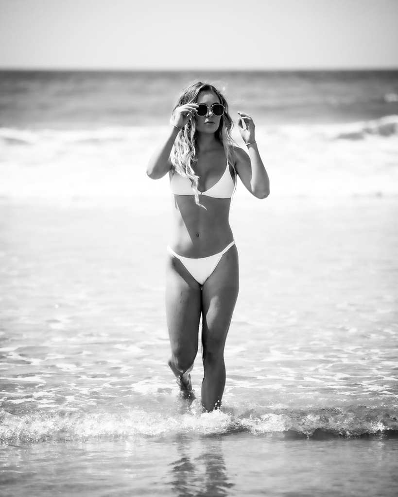 a woman walks through the beach water holding her sunglasses
