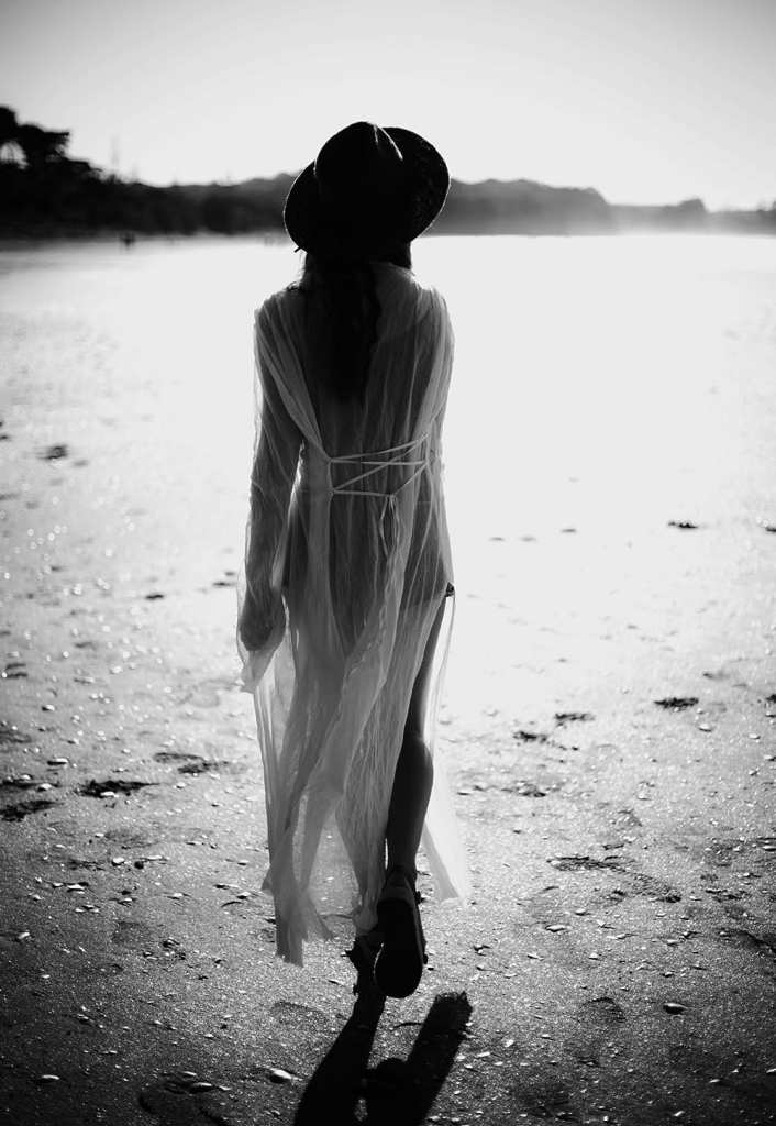 A black and white photo of a woman with her back turned as she walks on a beach