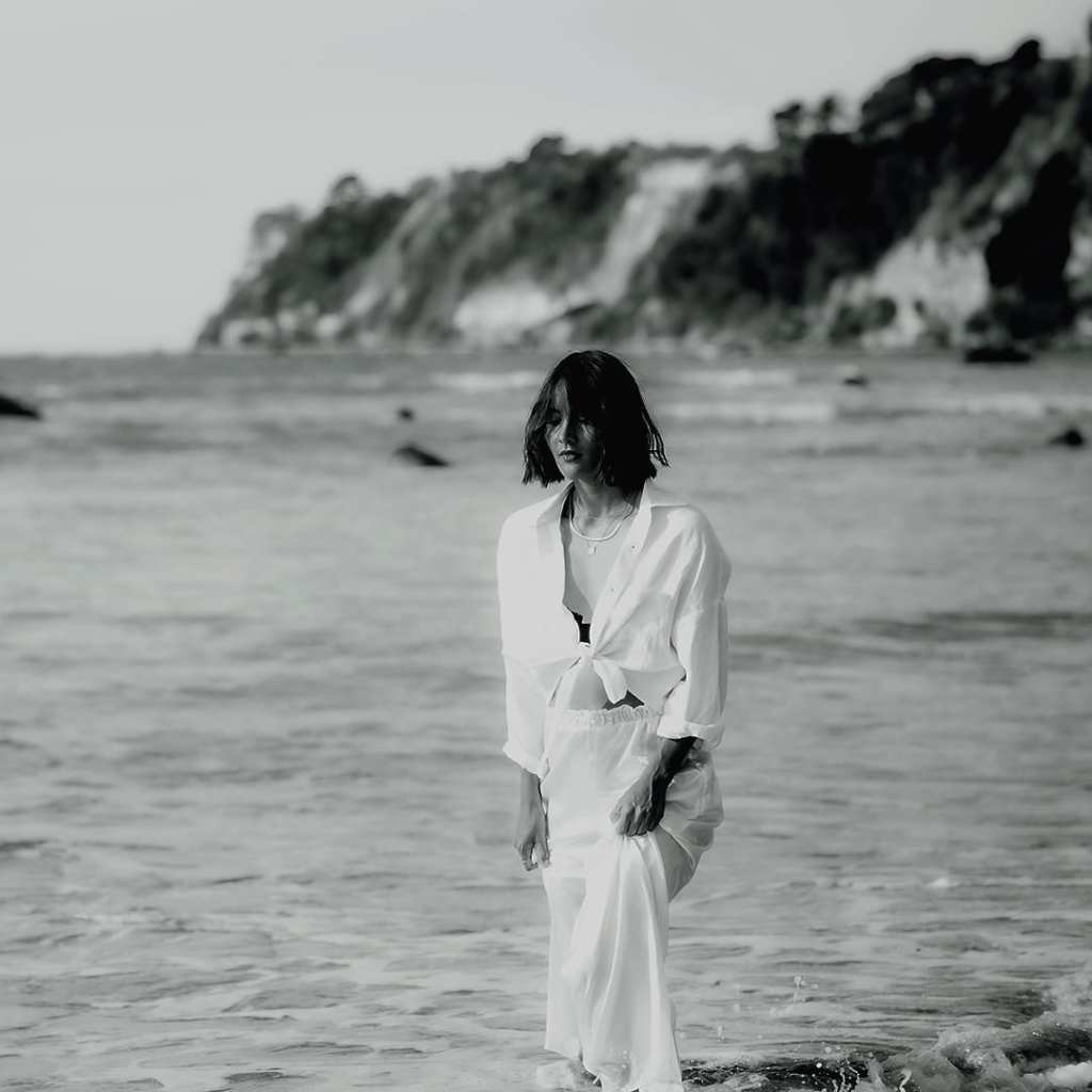 a woman in a white suit walks along a beach