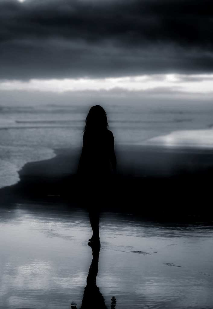a silhouette of a woman on a beach