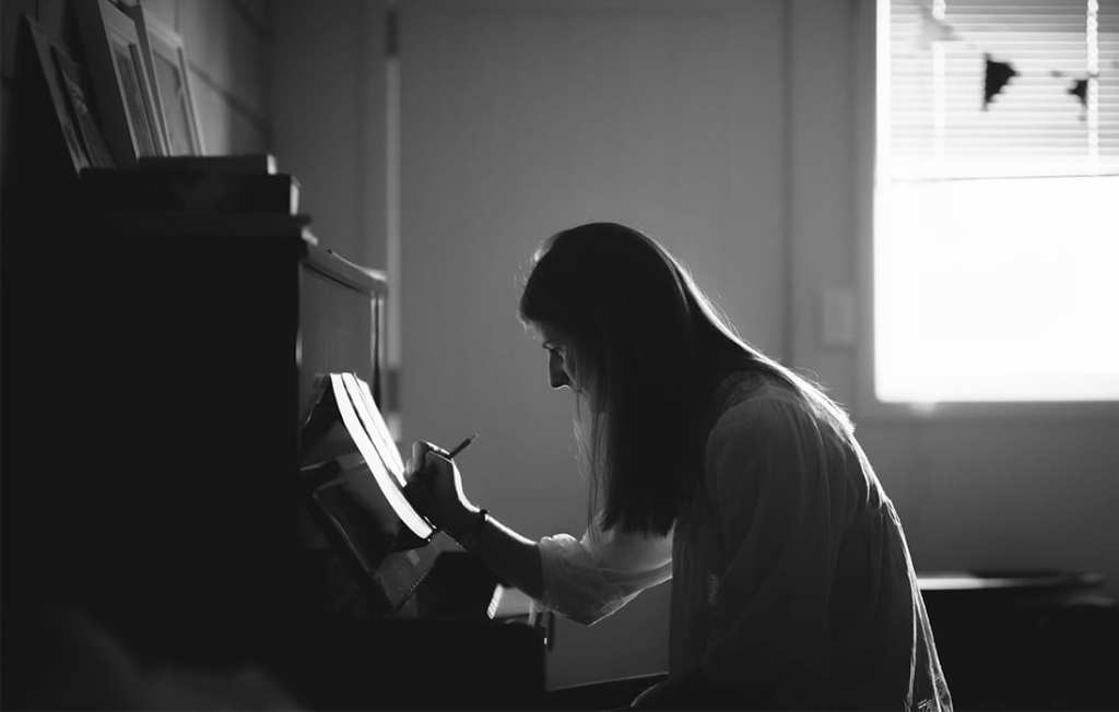 A black and white photograph of a woman sitting at a piano writing music
