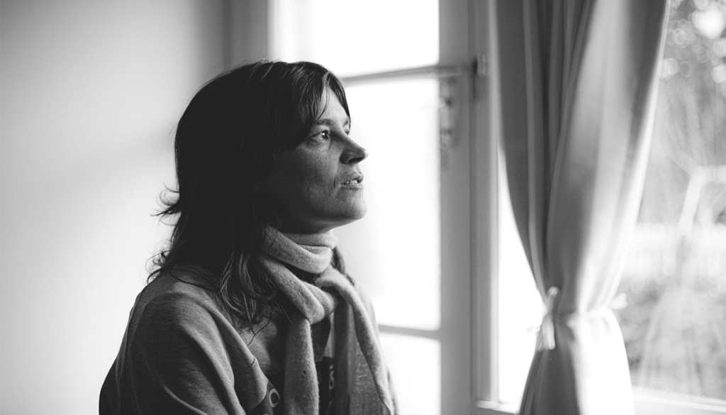 a black and white photo of a woman looking out of a window