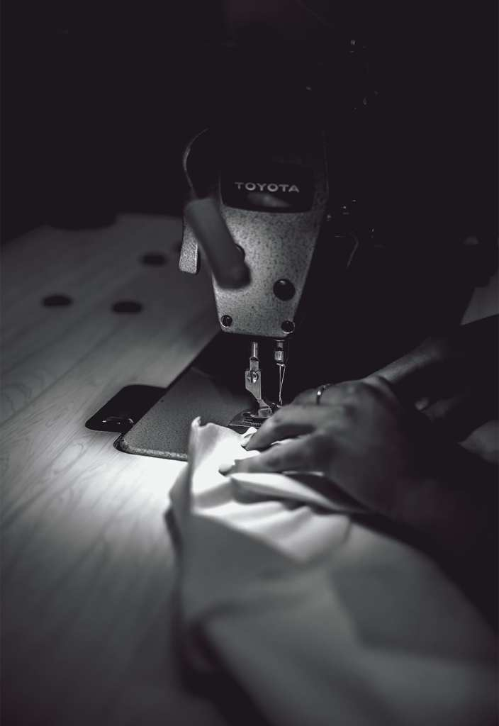 A black and white photo of a sewing machine with fabric
