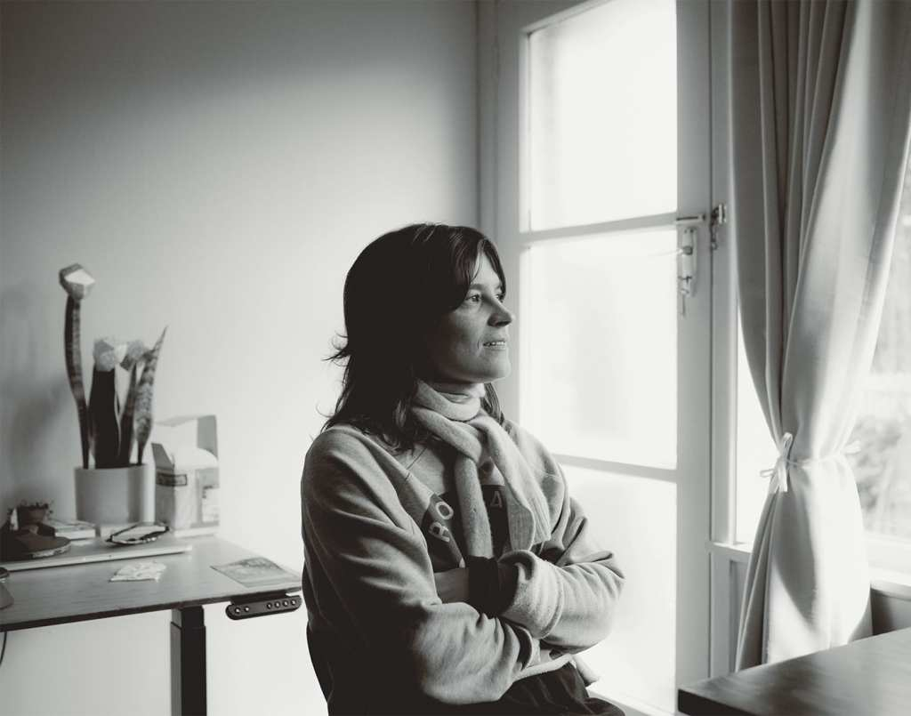 A black and white photo of a woman with dark hair sitting at a table looking out the window