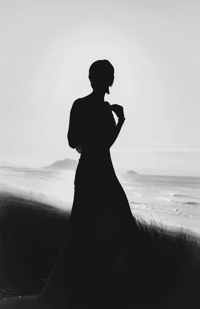 a silhouette of a woman standing on a beach