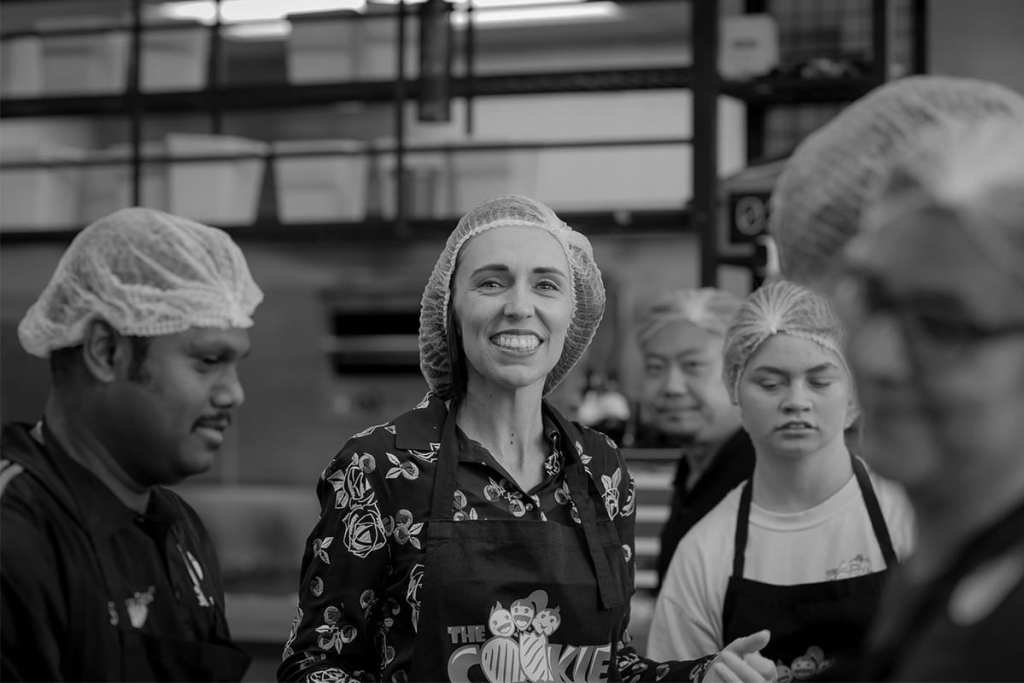 a woman wearing a hat in a kitchen smiles at the camera as she stands in a kitchen