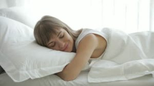 stock-footage-young-woman-sleeping-in-bed-waking-up-and-smiling-at-camera