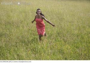 African woman running through field