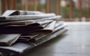several newspapers piled up on a table