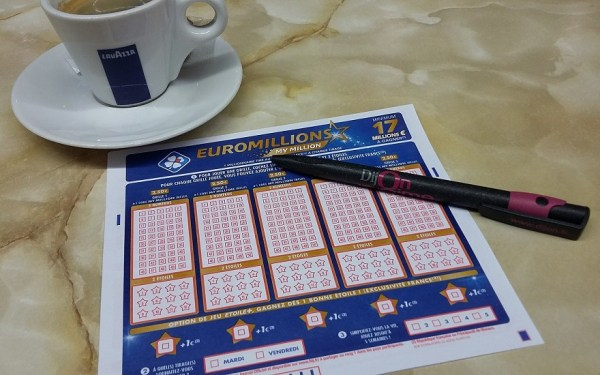 euromillions lottery ticket with a pen and a cup of coffee in a Lavaza branded mug