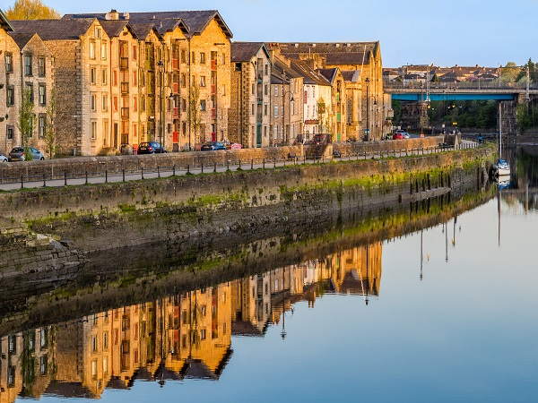 View from the Millenium Bridge in Lancaster across the River Lune to the buildings on the quayside.  Taken early morning on a crisp April morning with the warm sunlight on the buildings.