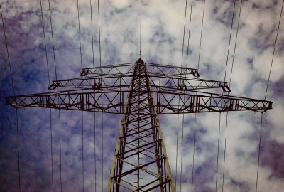 power transmission lines taken against a blue sky with clouds
