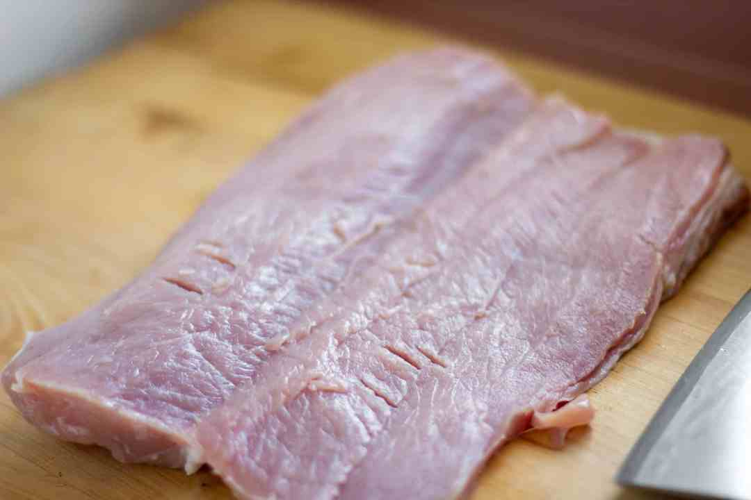 Trim the pork loin of any excess fat and butterfly it with a sharp knife.