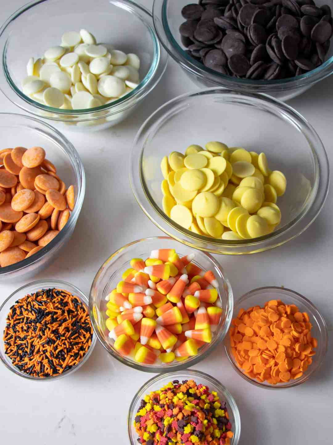 Overhead picture of bowls filled with ingredients of chocolate, sprinkles and candy corn.