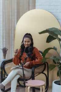 cheerful black woman recording voice on mic