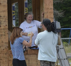 Meredith serves a cup of our Blockhouse Spirit Tea to CBC TV's Colleen Jones from the window of the Tiny Studio under construction, Aug. 16, 2013.