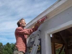 Lloyd applying caulking under the eaves.