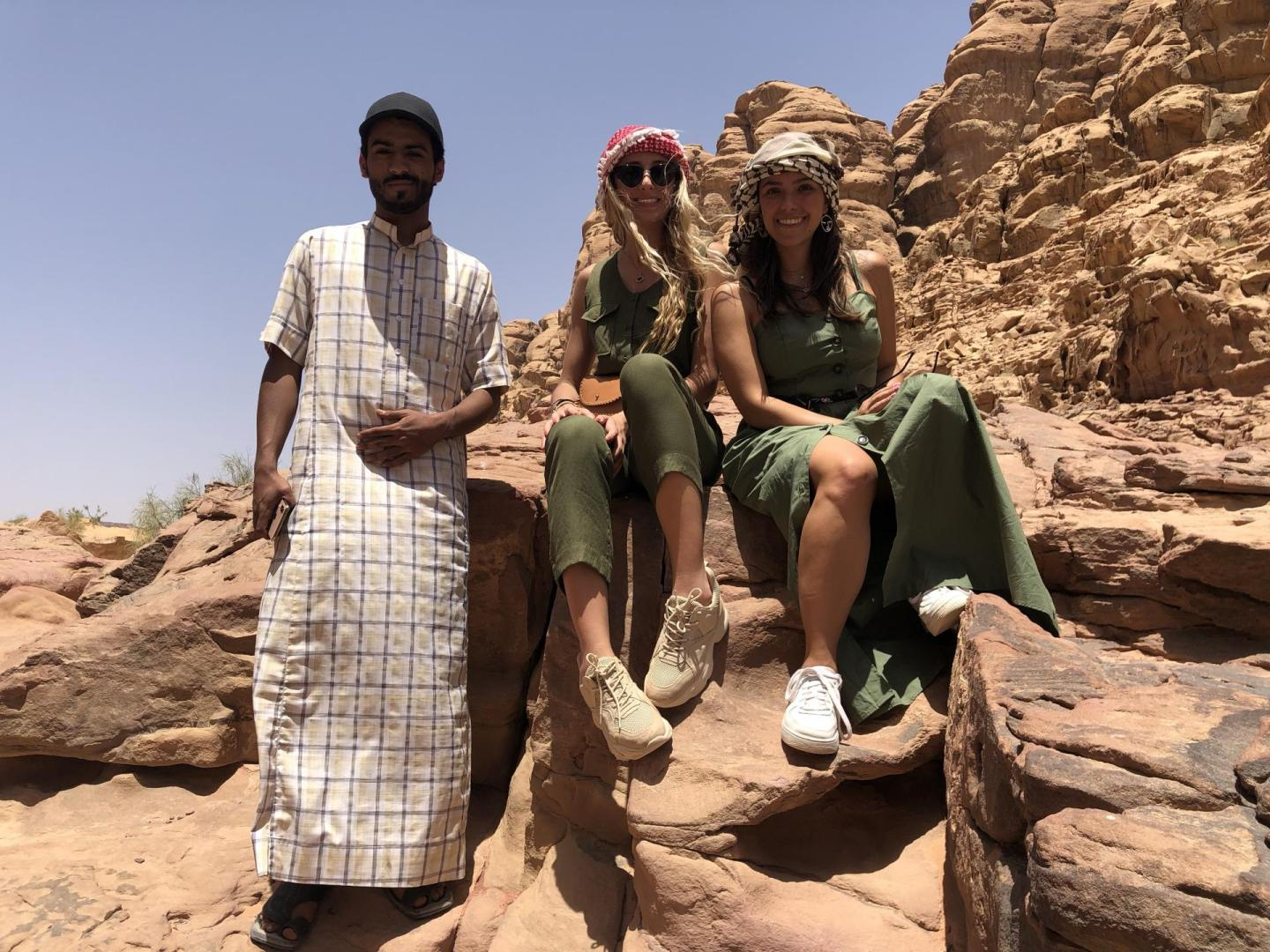 Two women and a Bedouin man in the desert.