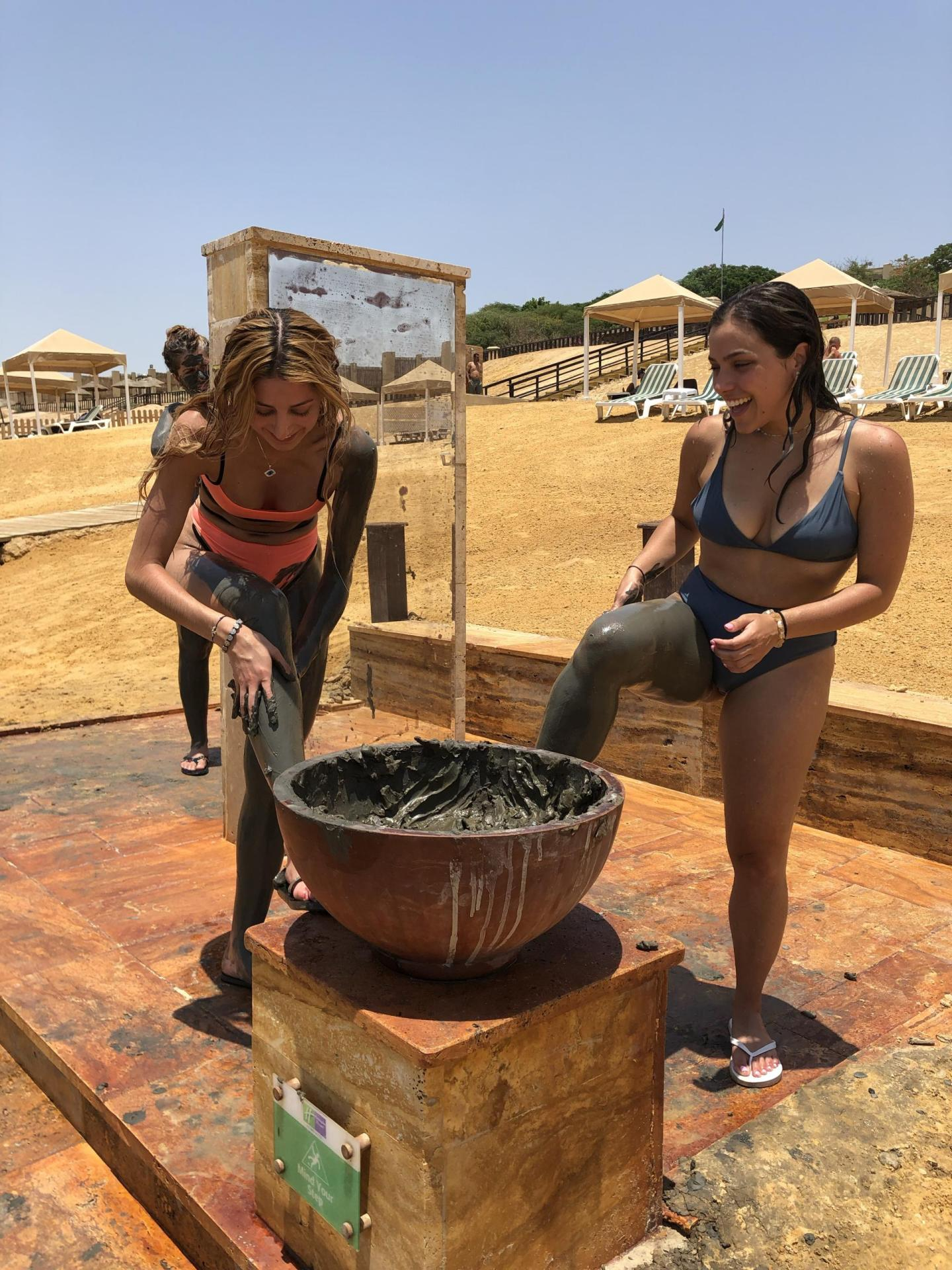Two women visiting the Dead Sea covering themselves in mud.