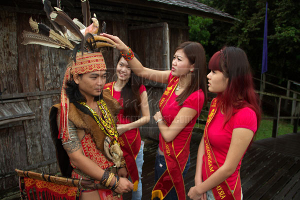 IS IT REAL?: Contestants take a look at a traditional headdress.