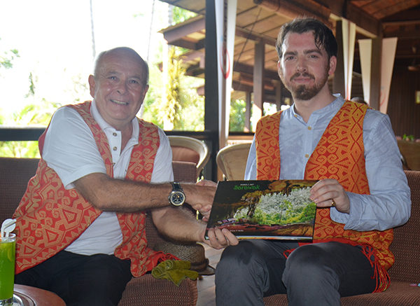 Aiman Batang Ai Resort and Retreat general manager Keith Pointer hands over a book  on parks and arts in Sarawak to Brooke after the signing ceremony.