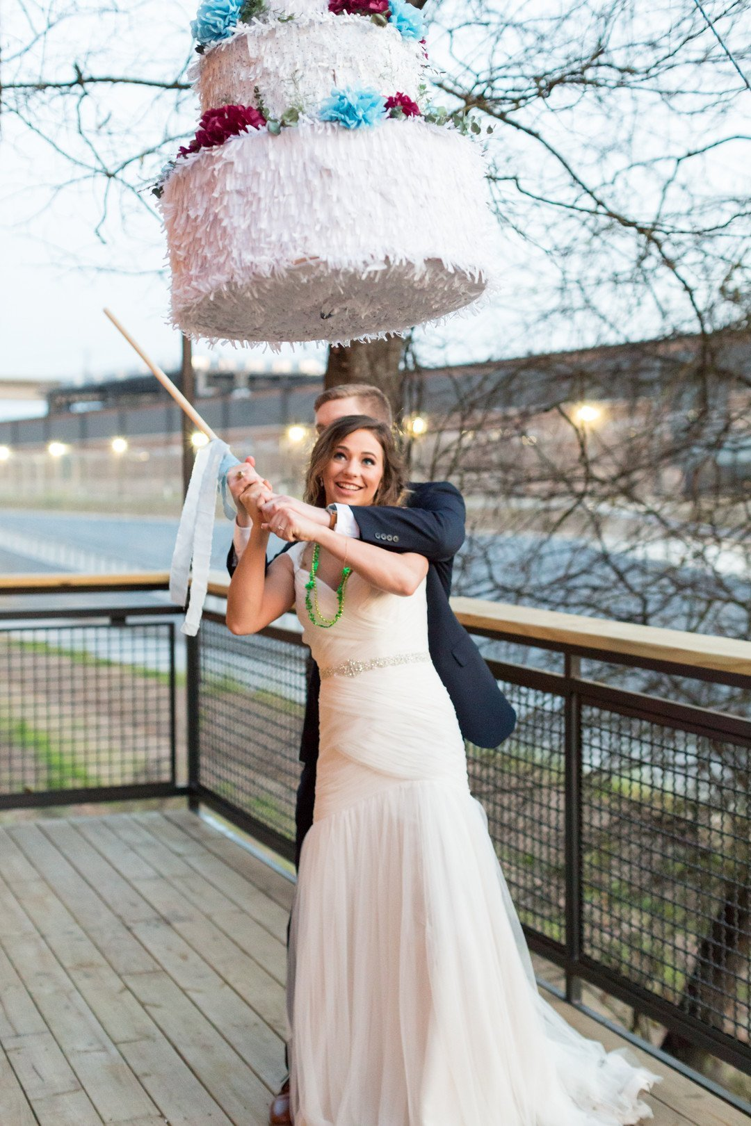 Bride and groom smashing wedding cake pinata