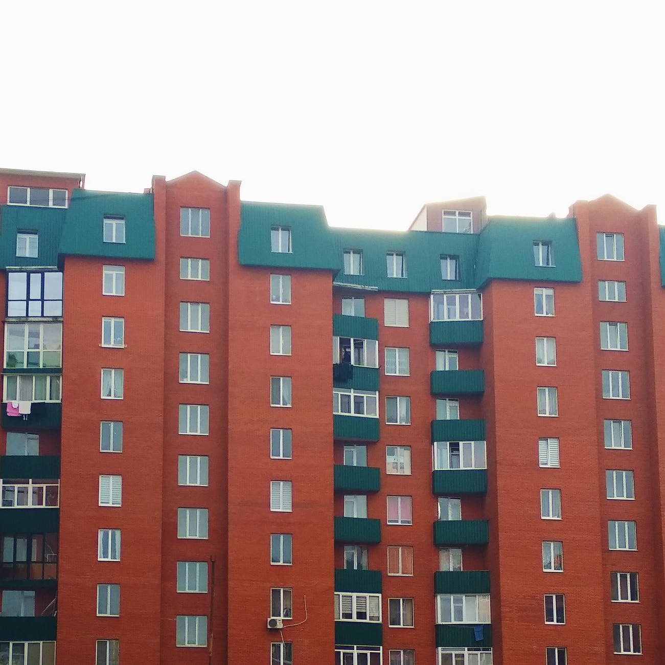 modern block of flats with green roof and balconies