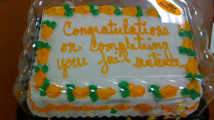 """A celebration cake with """"Congratulations on completeing your jail sentence"""" written on it in icing"""