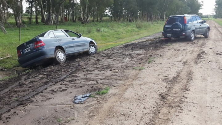 A car being towed off the edge of a muddy road