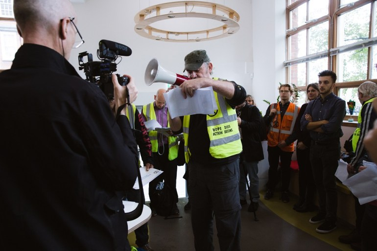 An activist with a megaphone at the Greenpeace office