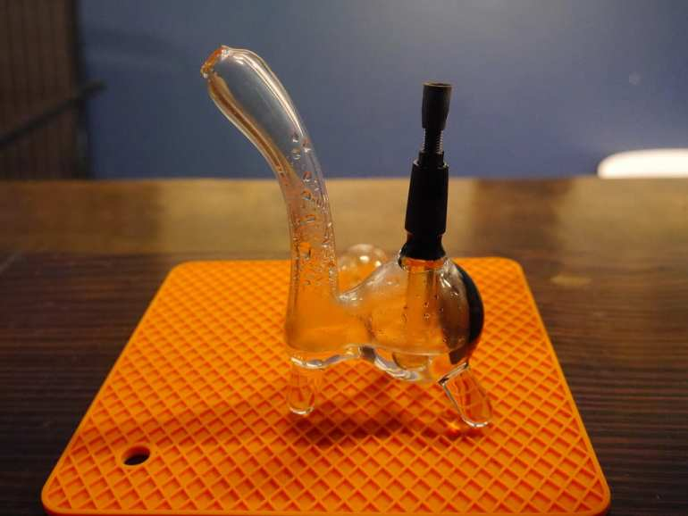 A glass dab rig is on a wooden table. This is used to smoke weed out of.