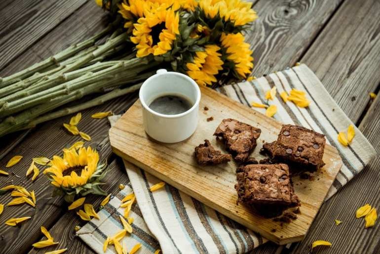 cannabis CBD brownies and cup of coffee on a cutting board. The cutting board is on a table with sunflowers beside it.