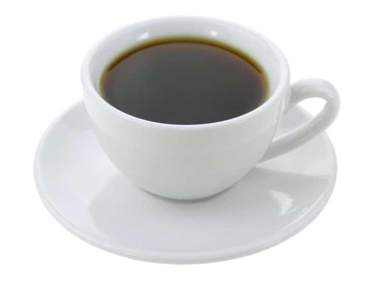White coffee mug with brown hot coffee inside, mixed with kief.