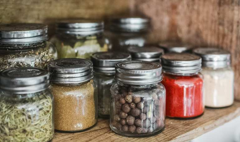 Cannabis edibles being stored on a shelf in an organized manner. All weed edibles are stored in mason jars.