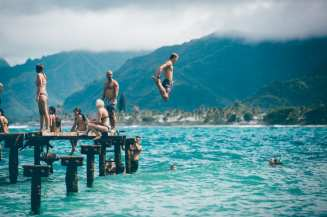 Activities to do high with your friends. Blue water with friends jumping off the dock.