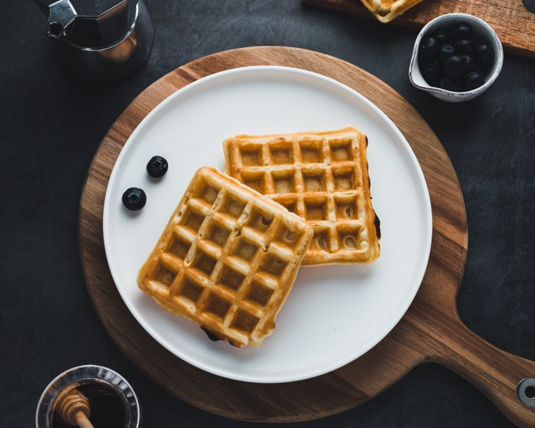 blueberry weed waffles on a white plate. the white plate has 2 blueberries on it. the plate is on a whie cutting board with honey and blueberries beside it on the table