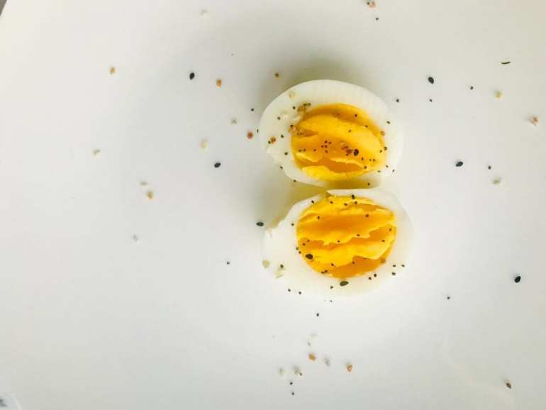 2 weed infused devilled eggs on a white backdrop. Salt, pepper, and other spices on the eggs and the table
