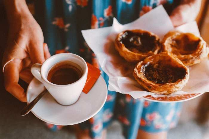 Woman holding a cup of coffee and a plate in one hand and cannabis infused butter tarts on a plate in the other